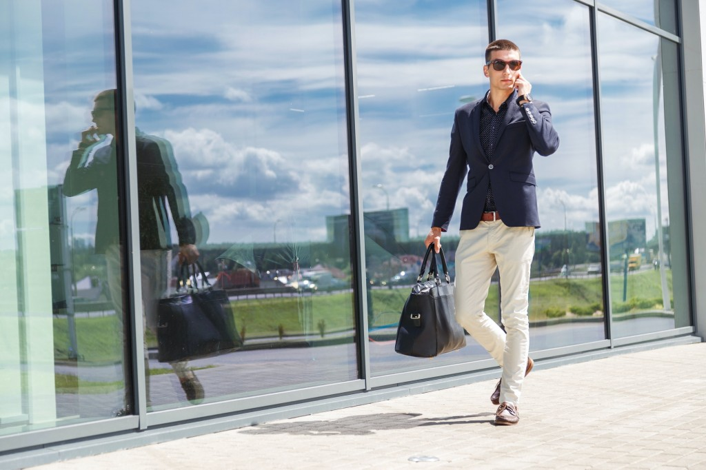 Elegant businessman call on mobile phone while walking with suitcase outside airport